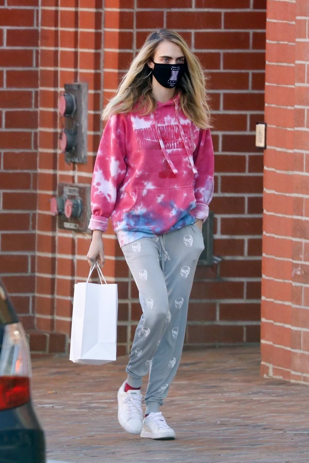 Cara Delevingne sports a pink tie-dye hoodie and grey sweatpants as she visits a medical building in Los Angeles