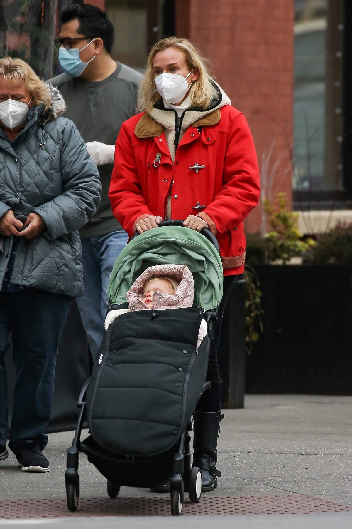 Diane Kruger bundles up in a red jacket and black leather boots for an outing with her mother and her daughter in New York City