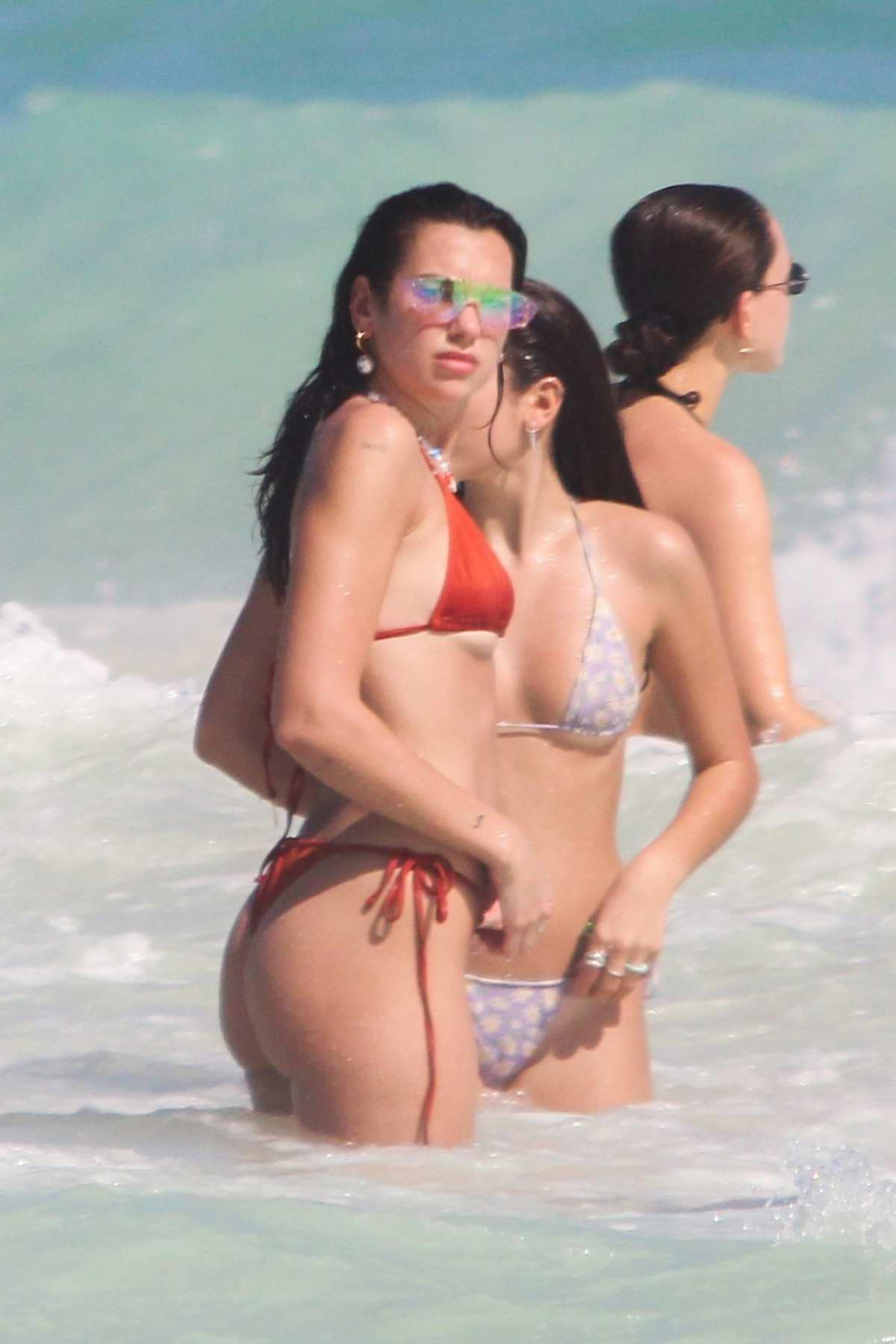 Dua Lipa shows off her sensational body in an orange bikini while enjoying the beach with friends in Tulum, Mexico