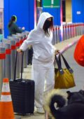 Emily Ratajkowski bundles up in a white sweatsuit as she and Sebastian Bear-Mclard arrive at Newark airport in Newark, New Jersey
