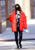 Emily Ratajkowski wears a red puffer jacket and black leggings as she steps out to walk her dog in New York City