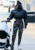 Gigi Hadid bundles up in a cropped puffer jacket, beanie and colorful pants while out for a stroll with her in New York City