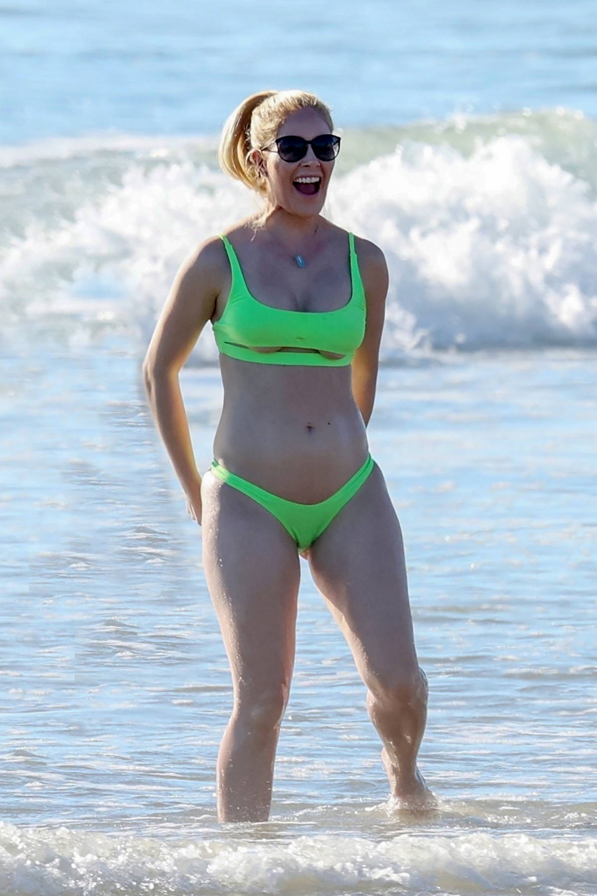 Heidi Montag sparks pregnancy rumors as she frolics on the beach wearing a green bikini in Carpinteria, California