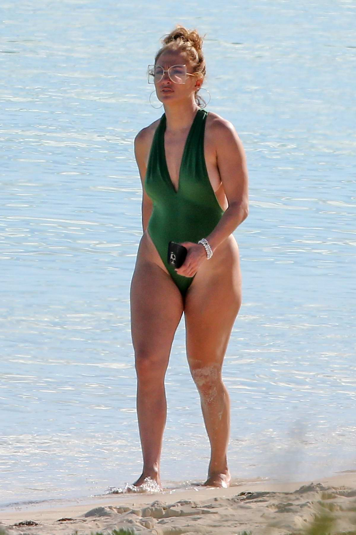 Jennifer Lopez shows off her curves in a green swimsuit while on the beach in Turks and Caicos
