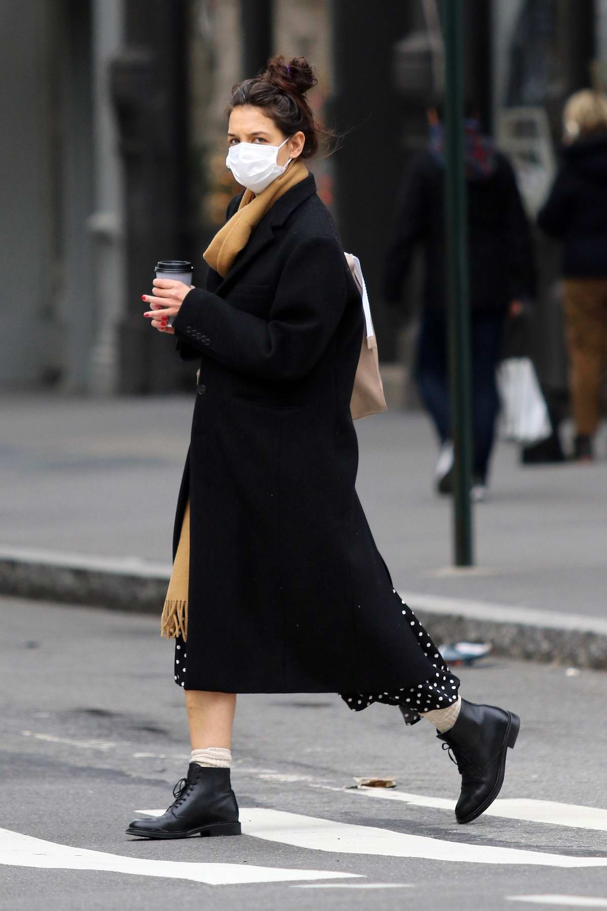 Katie Holmes bundles up in a black polka dot dress underneath a trench coat and scarf for a cold day in New York City