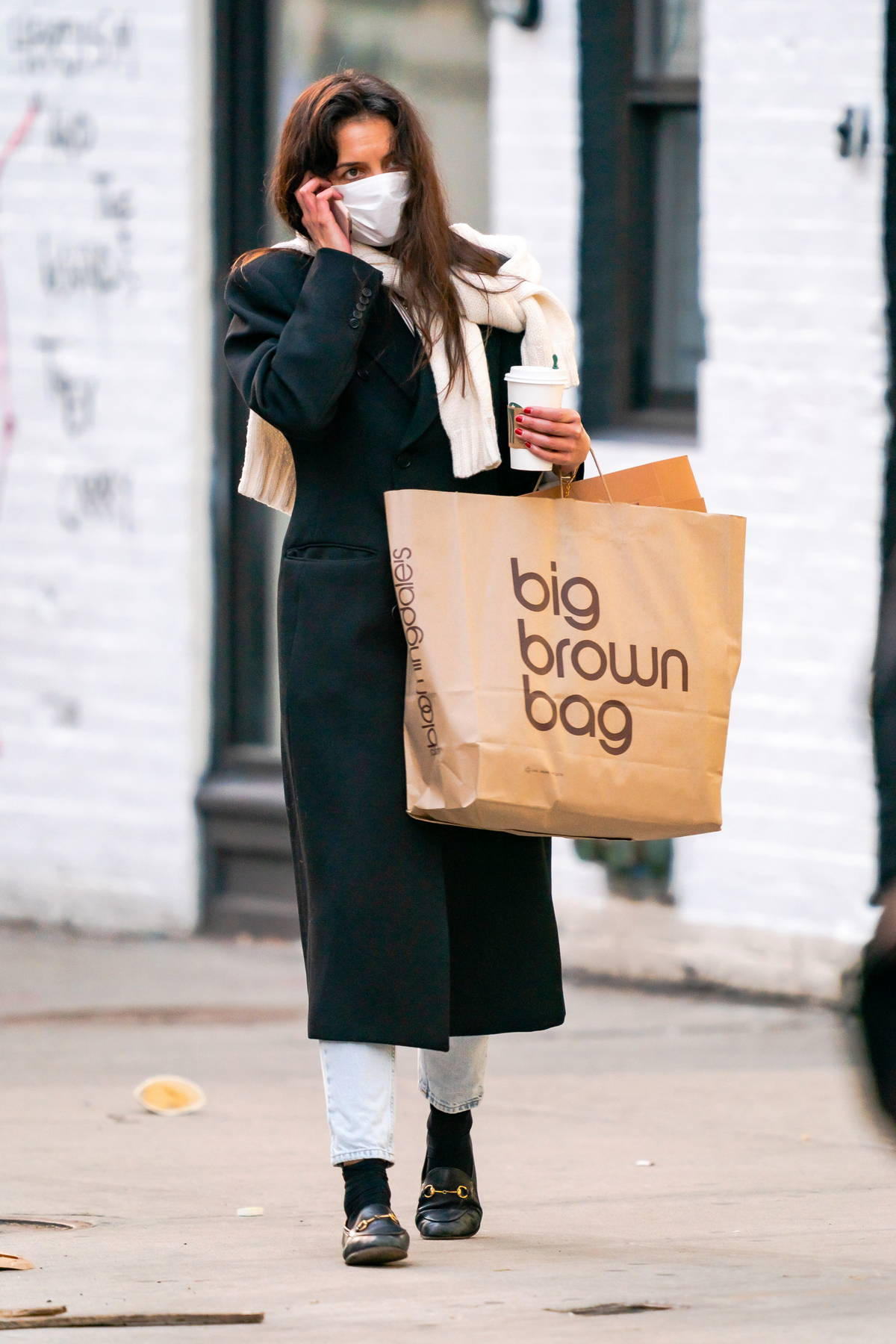 Katie Holmes looks cozy in a full-length wool coat as she enjoys a cup of Starbucks while out shopping in New York City