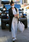Katie Holmes seen wearing Common Projects tennis shoes, white khaki pants with a leather coat while out in New York City