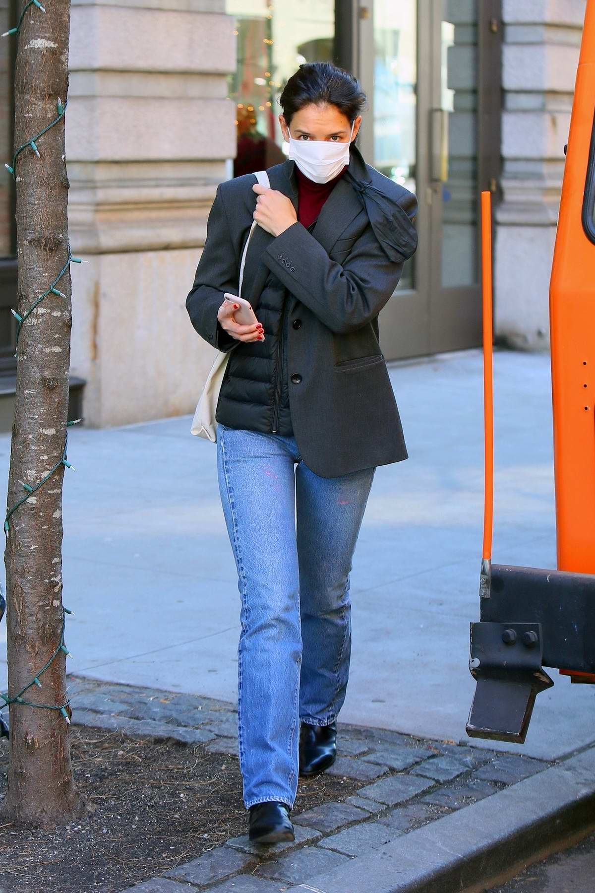 Katie Holmes wears a grey blazer over a puffer jacket while out catching an Uber in Soho, New York City