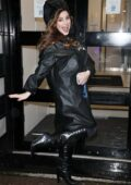 Kelly Brook dances in the rain in knee-high boots and a black coat during a downpour at the Global Radio Studios in London, UK