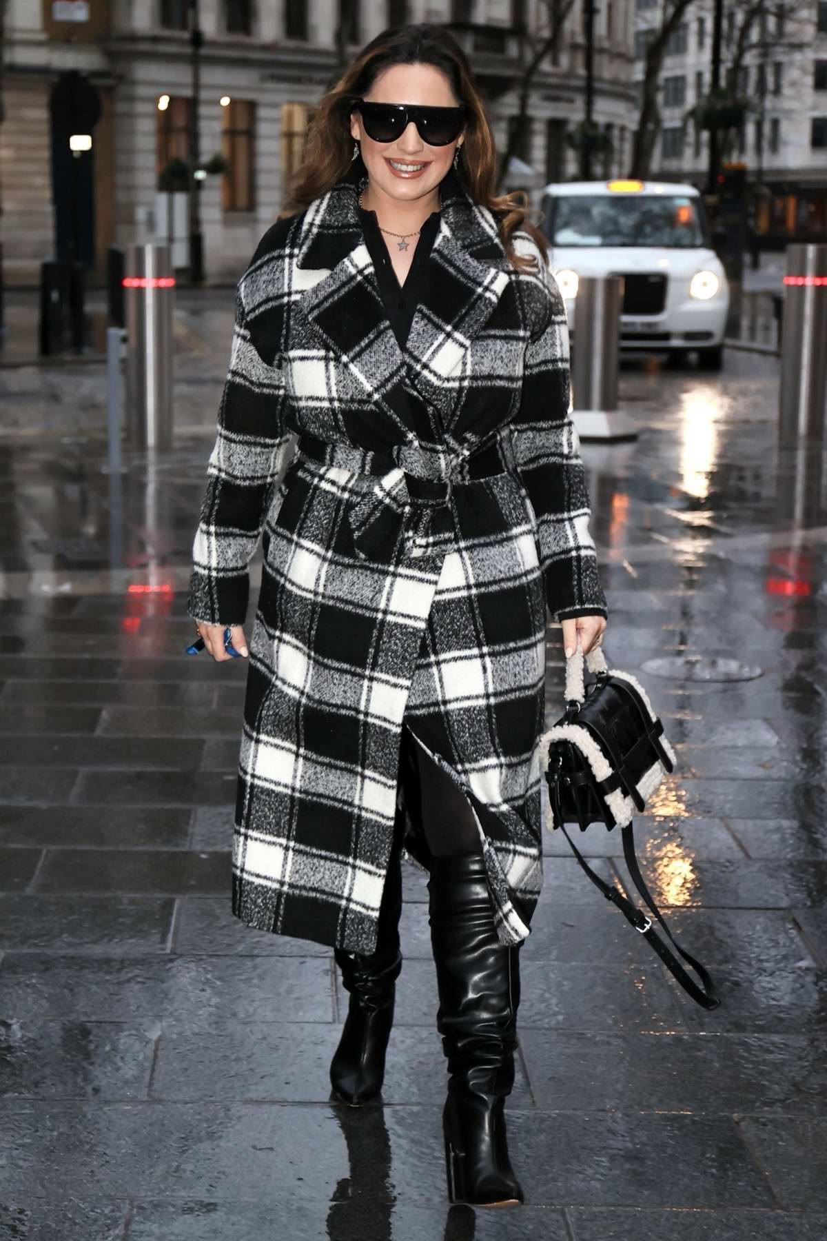 Kelly Brook looks chic in a checkered coat and boots outside the Heart Radio Studios in London, UK
