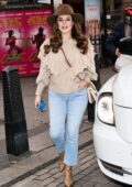 Kelly Brook wears a frilly beige sweater and jeans with a hat as she arrives at the Heart Radio in London, UK
