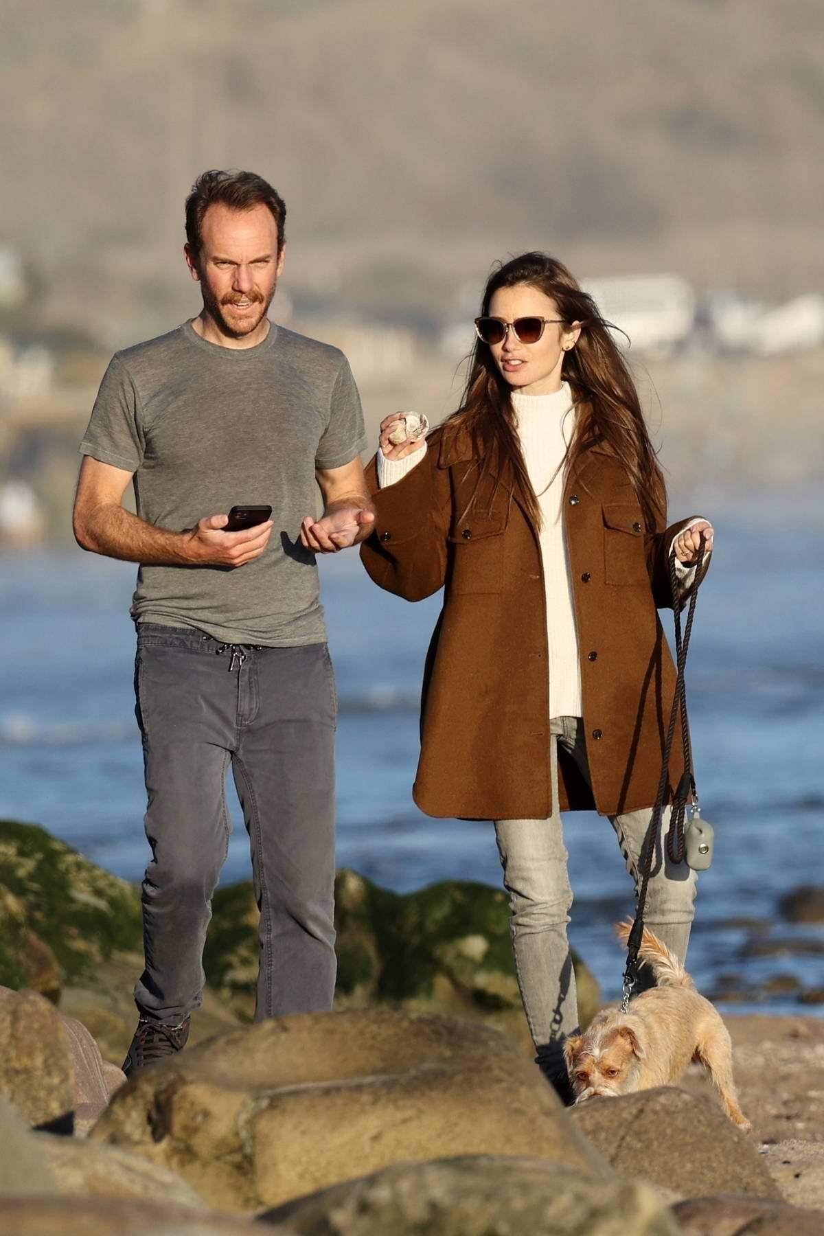 Lily Collins and Charlie McDowell enjoy a walk with their dog on a beach in Santa Barbara, California
