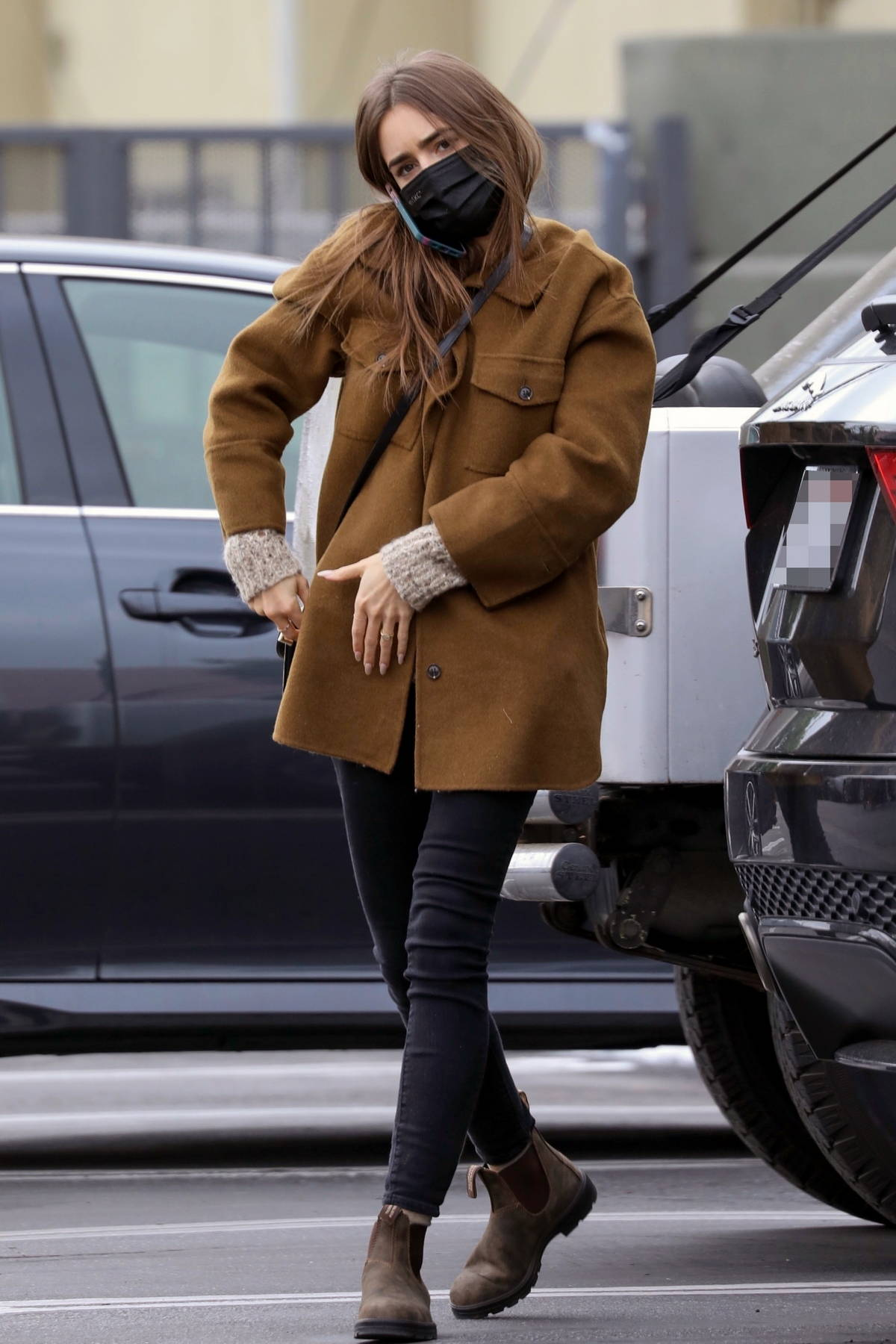 Lily Collins wears a brown jacket and black jeans as goes grocery shopping at Trader Joe's in Los Angeles
