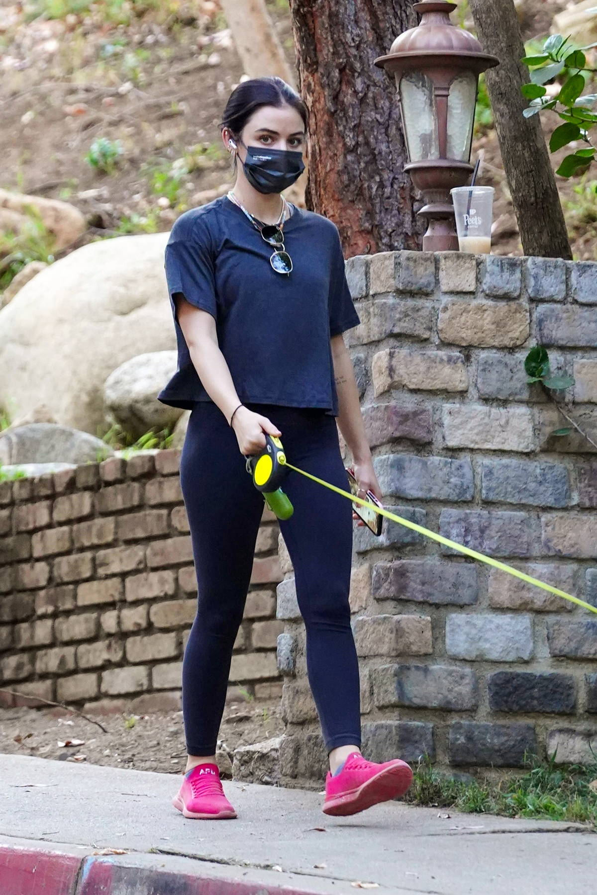 Lucy Hale dons a black tee and leggings while out for a hike with her pup in Los Angeles