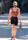 Lucy Hale shows off her fit figure in a maroon crop and black lycra shorts during a hiking session in Los Angeles