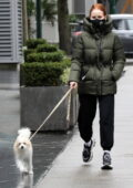 Madelaine Petsch bundles up in a olive geen puffer jacket while walking her dog in Vancouver, Canada