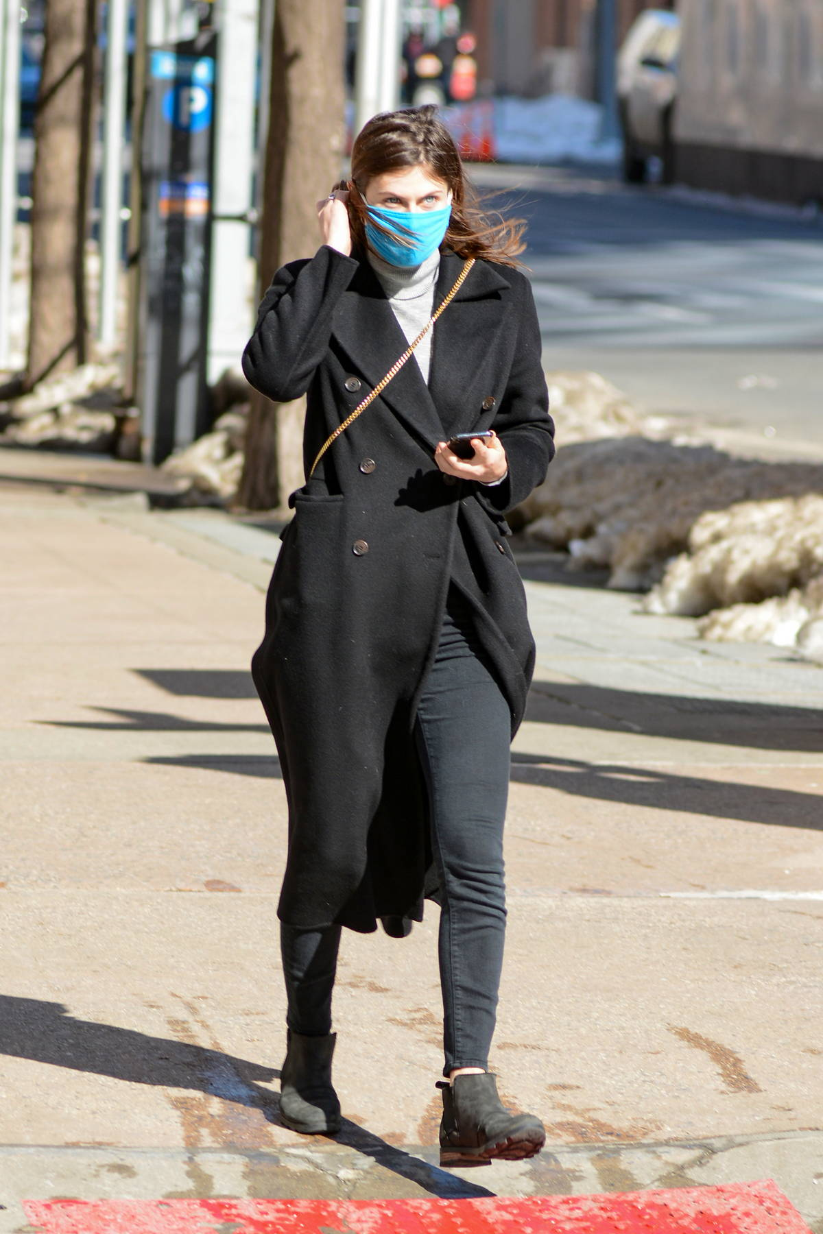 Alexandra Daddario steps out wearing a black overcoat on a windy day in New York City