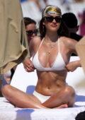 Amelia Hamlin soaks up the sun in a white bikini while enjoying the beach with Scott Disick on Valentine's Day in Miami, Florida