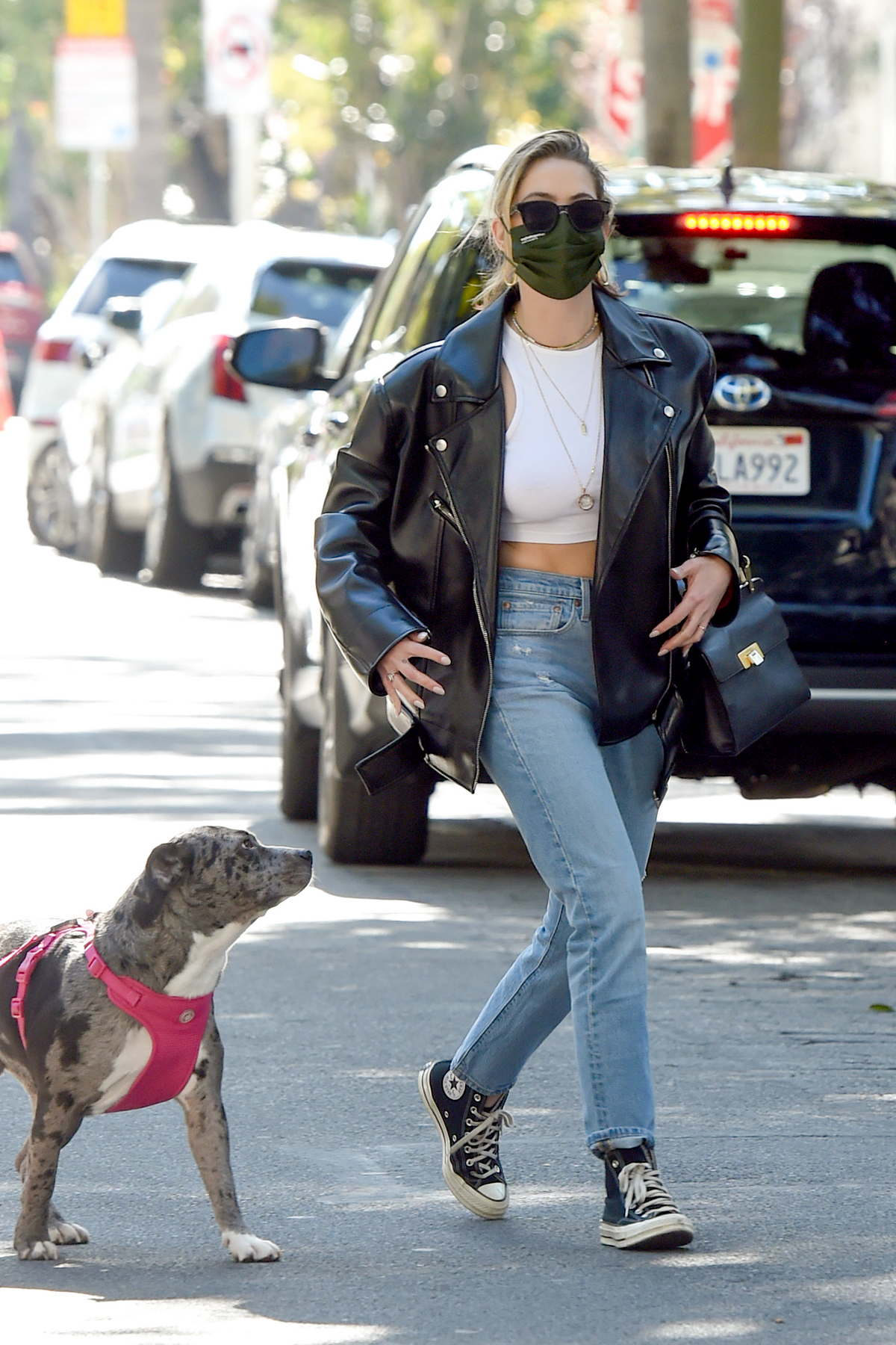 Ashley Benson wears a black leather jacket and jeans for a dog walk with a friend in Los Angeles