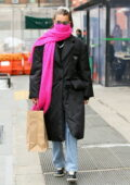 Bella Hadid wears a black Prada coat and a bright pink scarf as she heads out to lunch with friends in New York City