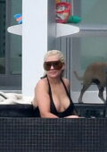 Christina Aguilera wears a black swimsuit as she takes a dip in the pool between sessions in Miami, Florida
