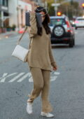 Eiza Gonzalez hides her face behind her Macbook as she leaves a salon in Los Angeles