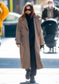Emily Ratajkowski wears a beige trench coat with a black hoodie and joggers while out while out on a stroll in New York City