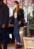 Hailey Bieber looks chic in a black leather jacket paired with a white top and jeans while out for lunch in Beverly Hills, California