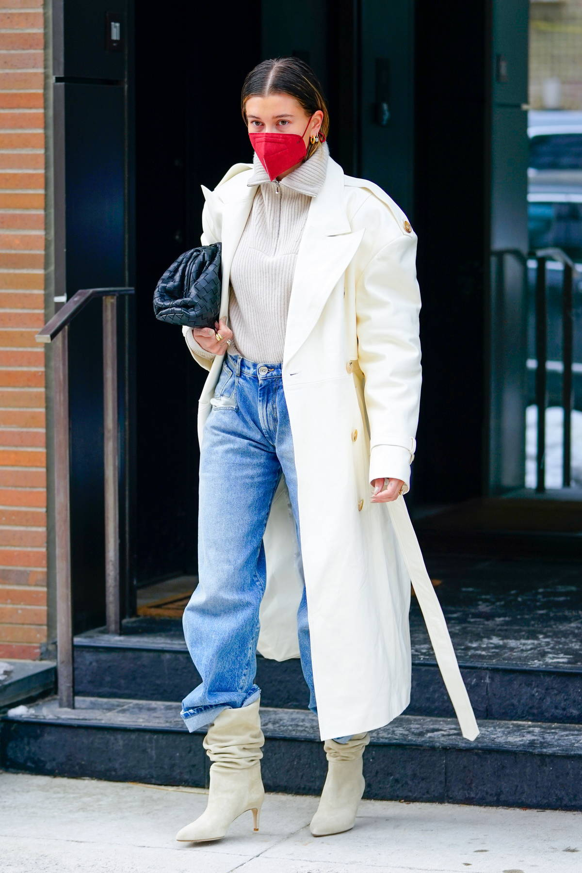 Hailey Bieber looks super chic in a white long coat paired with a cream sweater, jeans and boots as she heads out in Brooklyn, New York