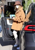 Hailey Bieber rocks a hat with an oversized tan jacket while arriving at a hair salon in Beverly Hills, California