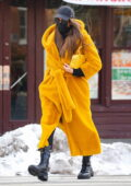 Irina Shayk looks striking in a yellow long puffy coat while out running errands in New York City