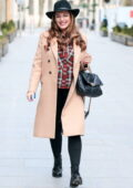Kelly Brook looks super glammed up with her wavy hair, tight denim and beige coat with a fedora hat in London, UK