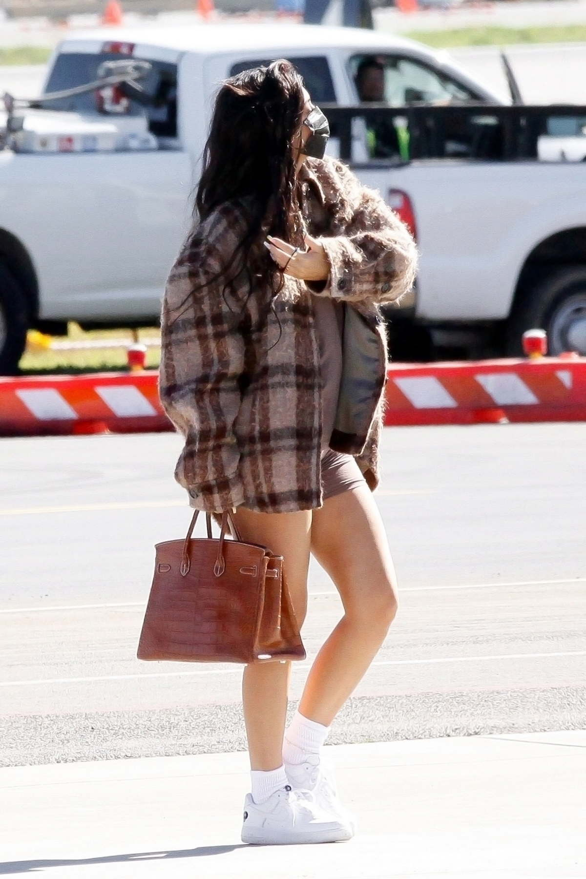 Kylie Jenner puts on a leggy display while boarding a private jet with her daughter Stormi in Los Angeles