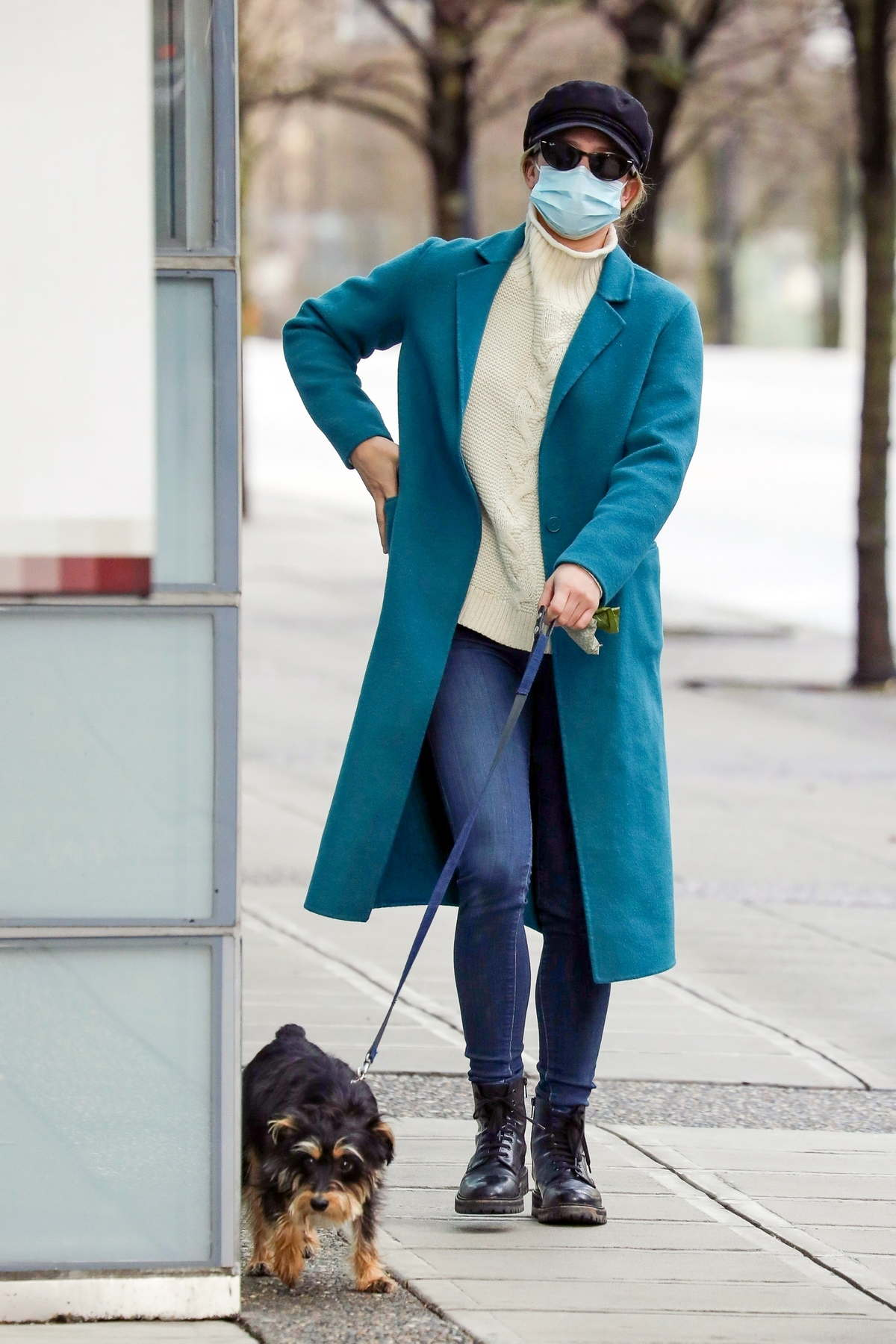 Lili Reinhart stays warm in a cream sweater and a turquoise coat while walking her dog in Vancouver, Canada