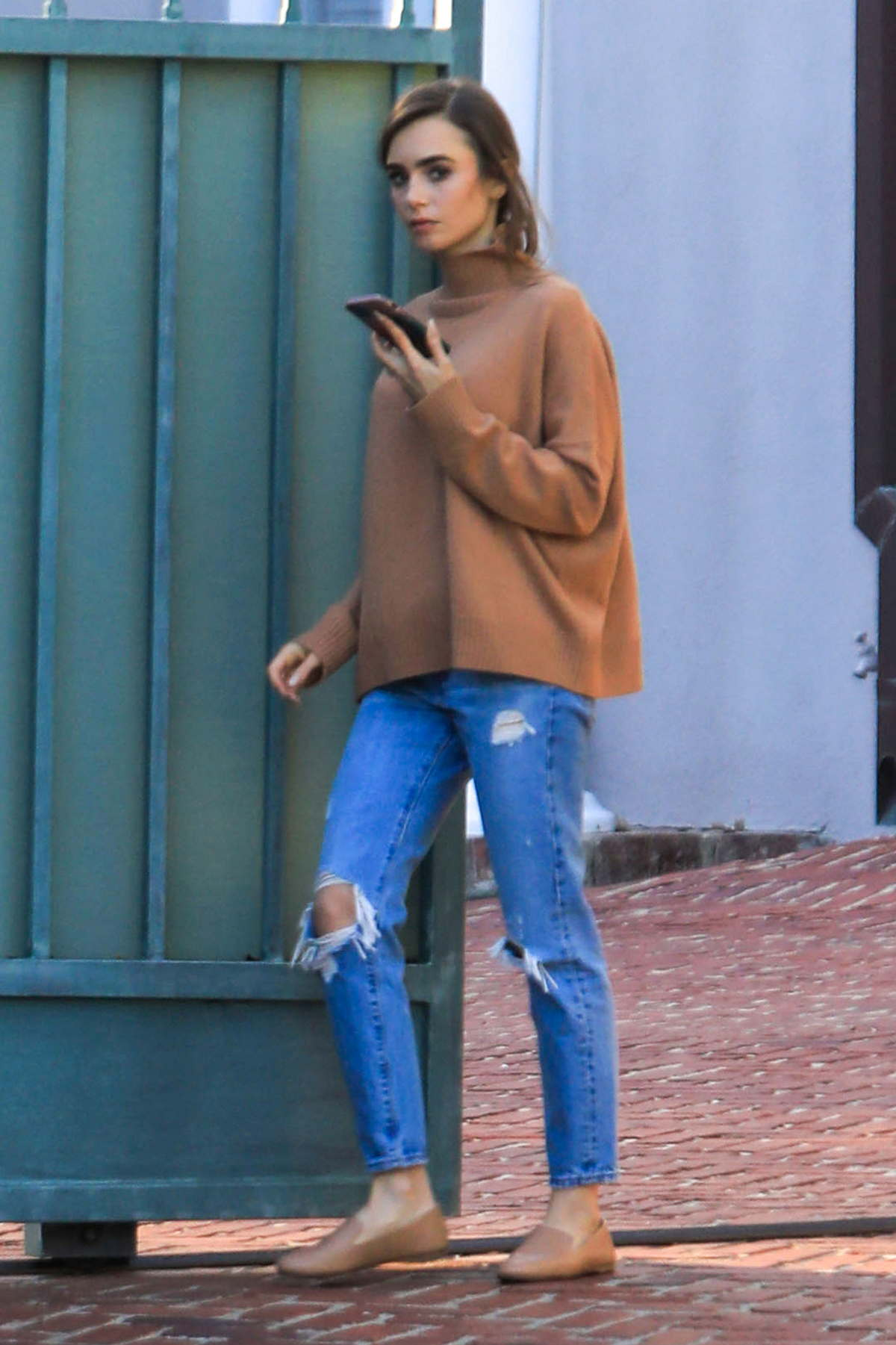 Lily Collins chats on her phone as she steps out wearing a brown sweater in Beverly Hills, California