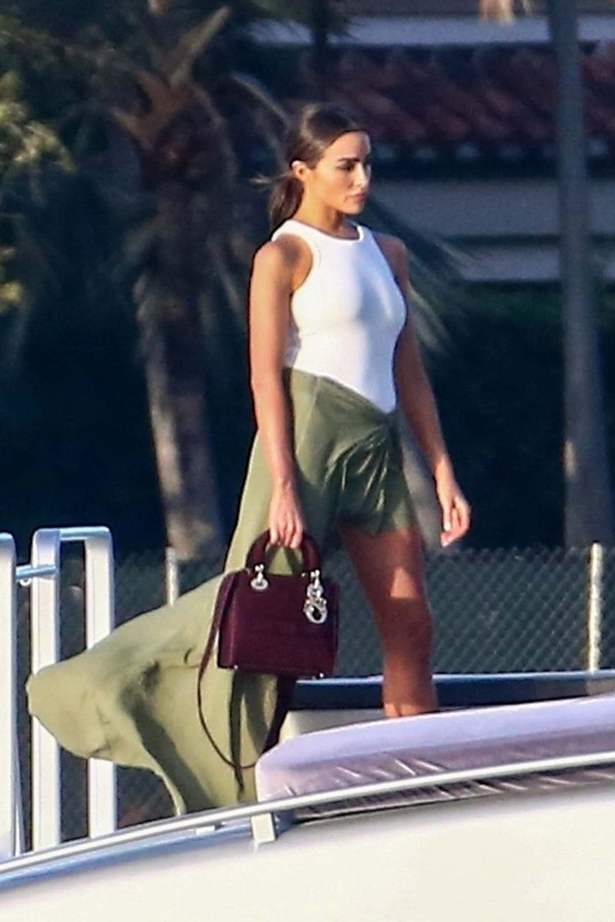 Olivia Culpo looks fab in white bodysuit and green wrap-skirt while enjoying a boat party in Miami Beach, Florida