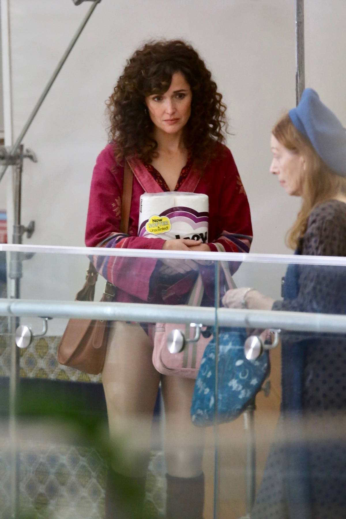 Rose Byrne holds a package of toilet paper while filming scenes for 'Physical' at a strip mall in Los Angeles
