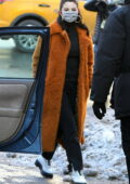 Selena Gomez seen wearing a long orange fur coat over a black outfit while on set of the 'Only Murders in the Building' in New York City
