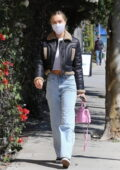 Alexis Ren looks good in a white crop top with a leather jacket and jeans while visiting P.volve studio in Los Angeles