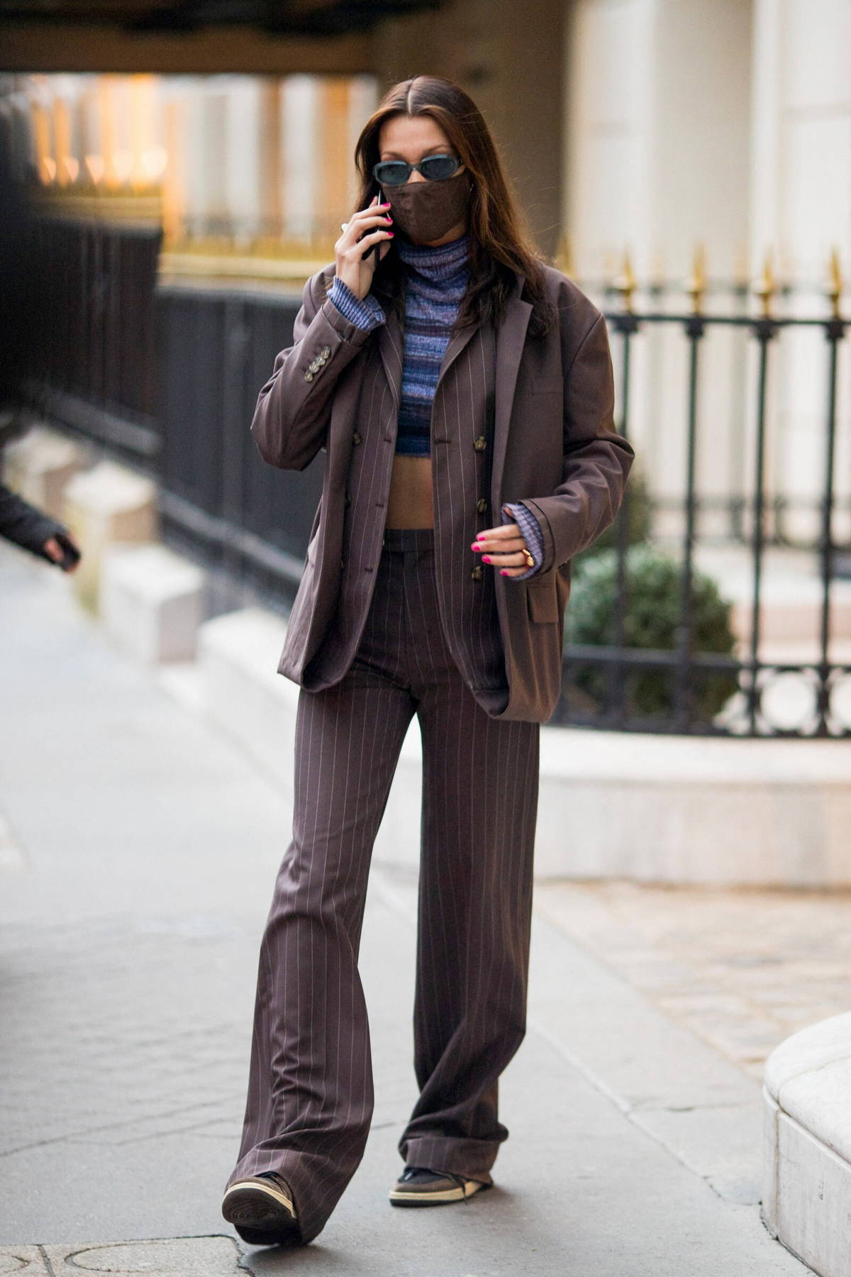 Bella Hadid shows off her abs while stepping out wearing a crop top with a pinstriped suit in Paris, France