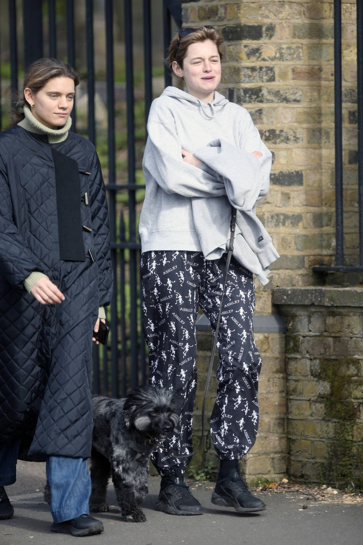 Emma Corrin keeps it casual as she steps out to walk her dog with a friend in London, UK