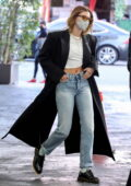 Hailey Bieber looks trendy in a full-length coat over a crop top while out running errands in Beverly Hills, California