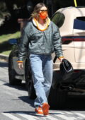 Hailey Bieber rocks a green jacket with an orange accent to match her mask and sneakers while visiting a friend in Los Angeles