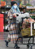 Hilary Duff covers up her baby bump in a plaid overcoat while shopping groceries in the rain in Los Angeles