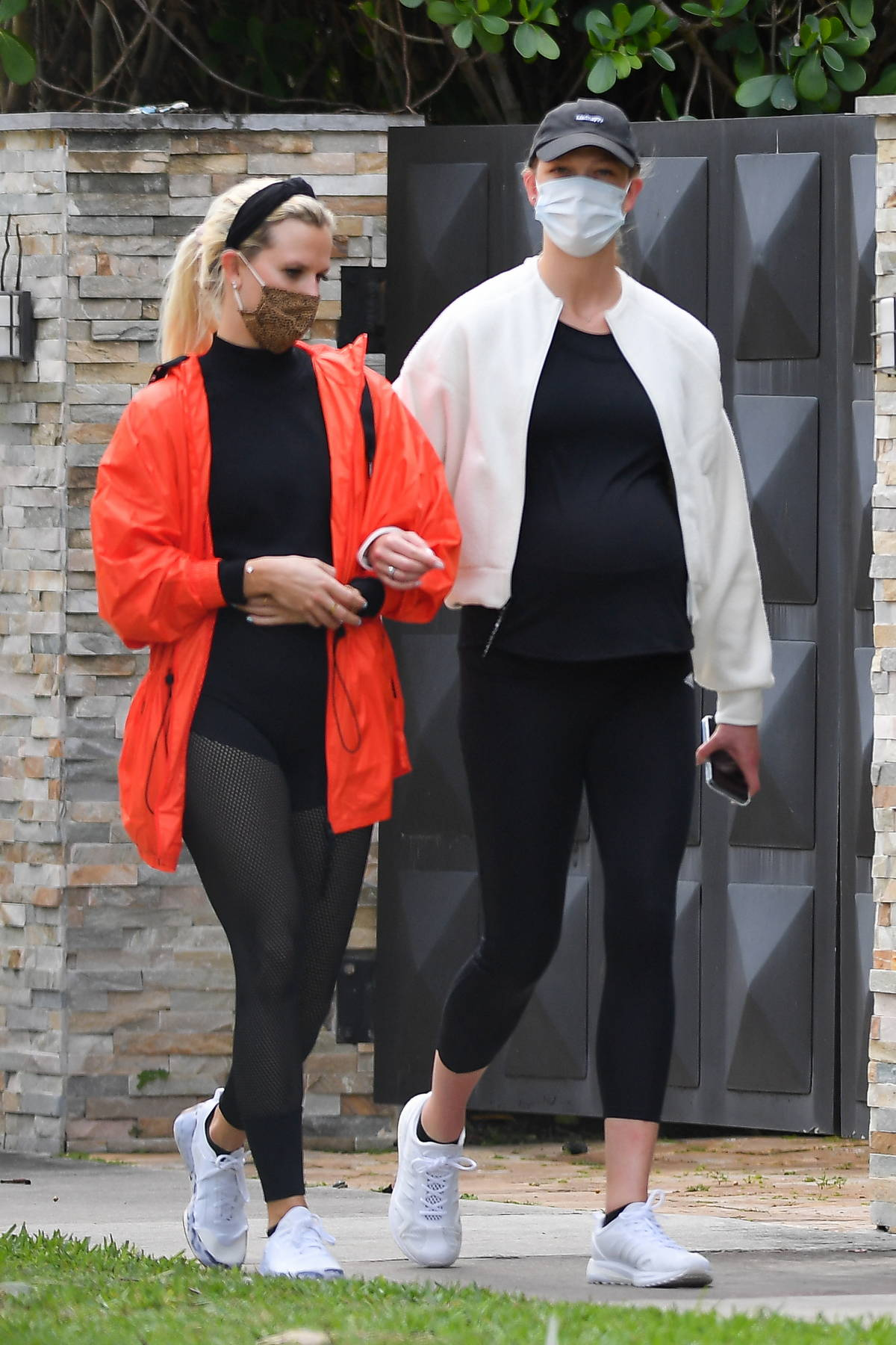 Karlie Kloss walks arm-in-arm with a friend while out for a stroll in Miami Beach, Florida