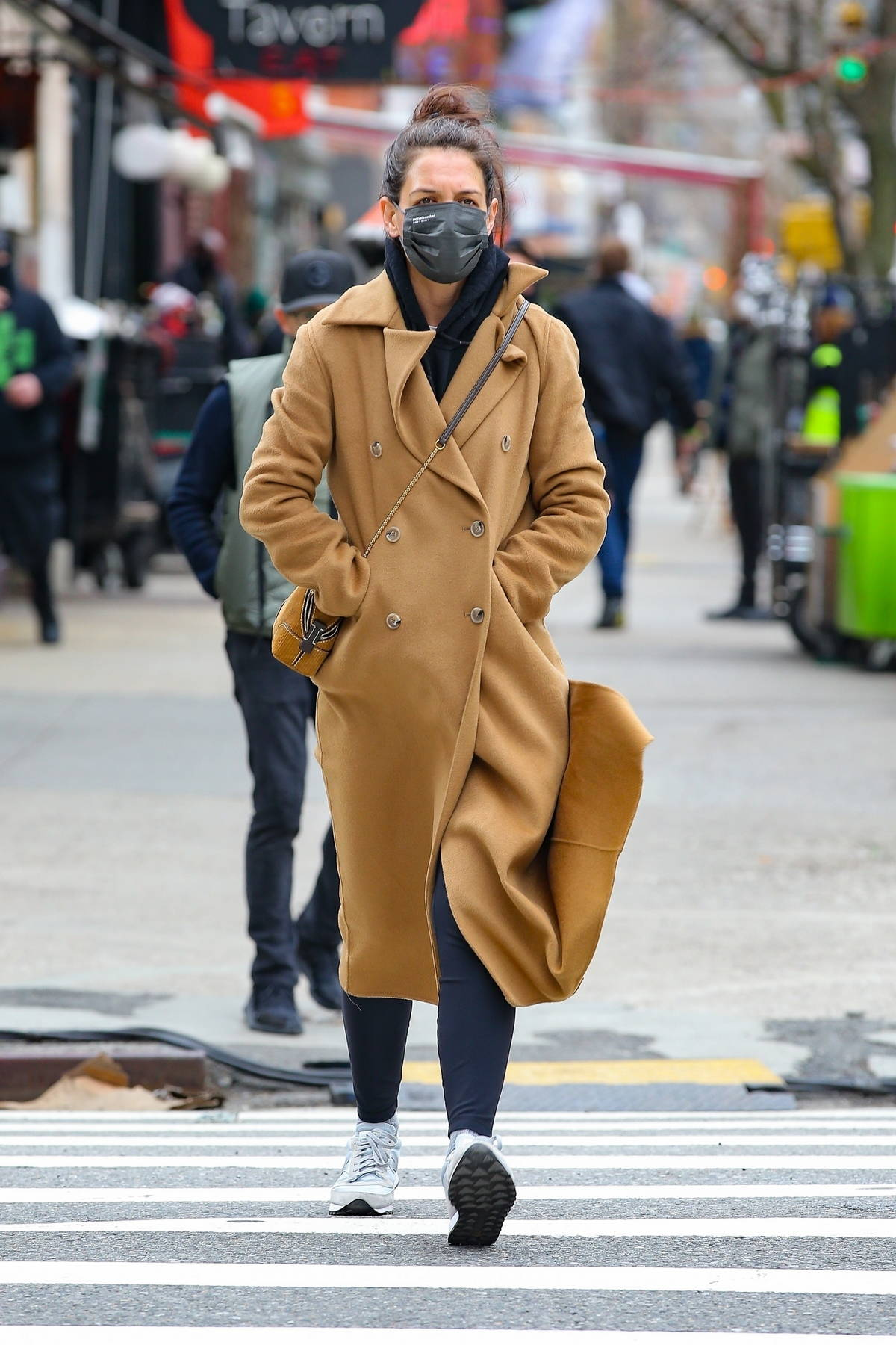 Katie Holmes bundles up in full-length coat over a hoodie and leggings while out for a stroll in New York City