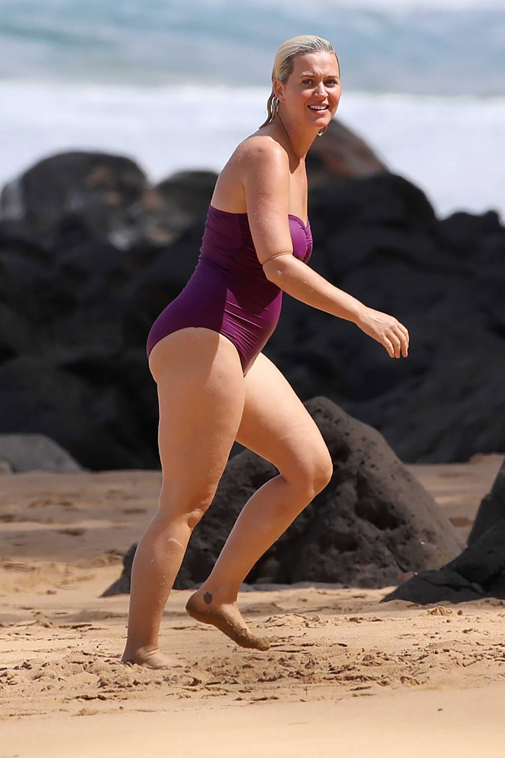 Katy Perry wears a purple swimsuit while enjoying a day at the beach while on vacation in Hawaii