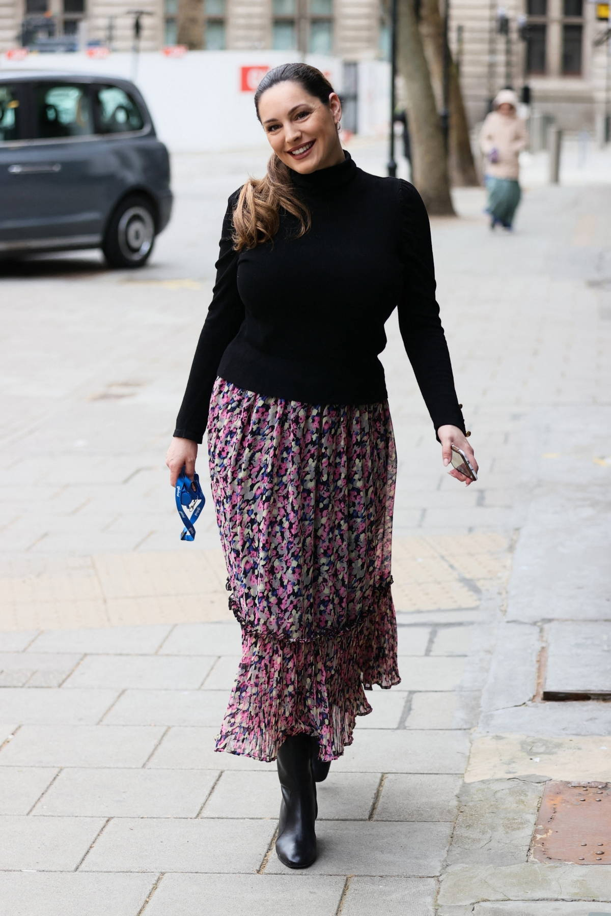 Kelly Brook wears a floral skirt and black jumper as she arrives for her show at Heart radio in London, UK