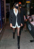 Kendall Jenner looks chic in a black and white blazer outfit with knee-high boots while heading out to dinner in New York City