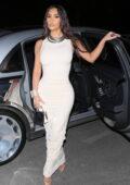Kim Kardashian looks stunning in a figure-hugging white dress as she arrives for dinner in Los Angeles